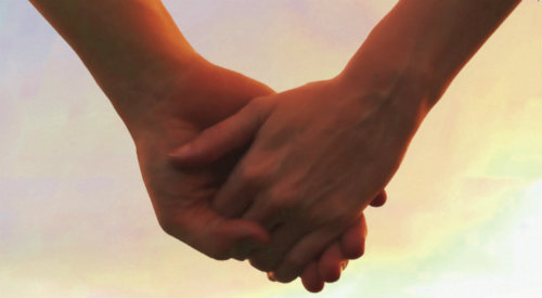 Close-up of holding hands in the sunset.