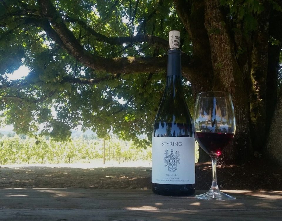 Styring Signature Pinot Noir Bottle and glass on picnic table near large tree.